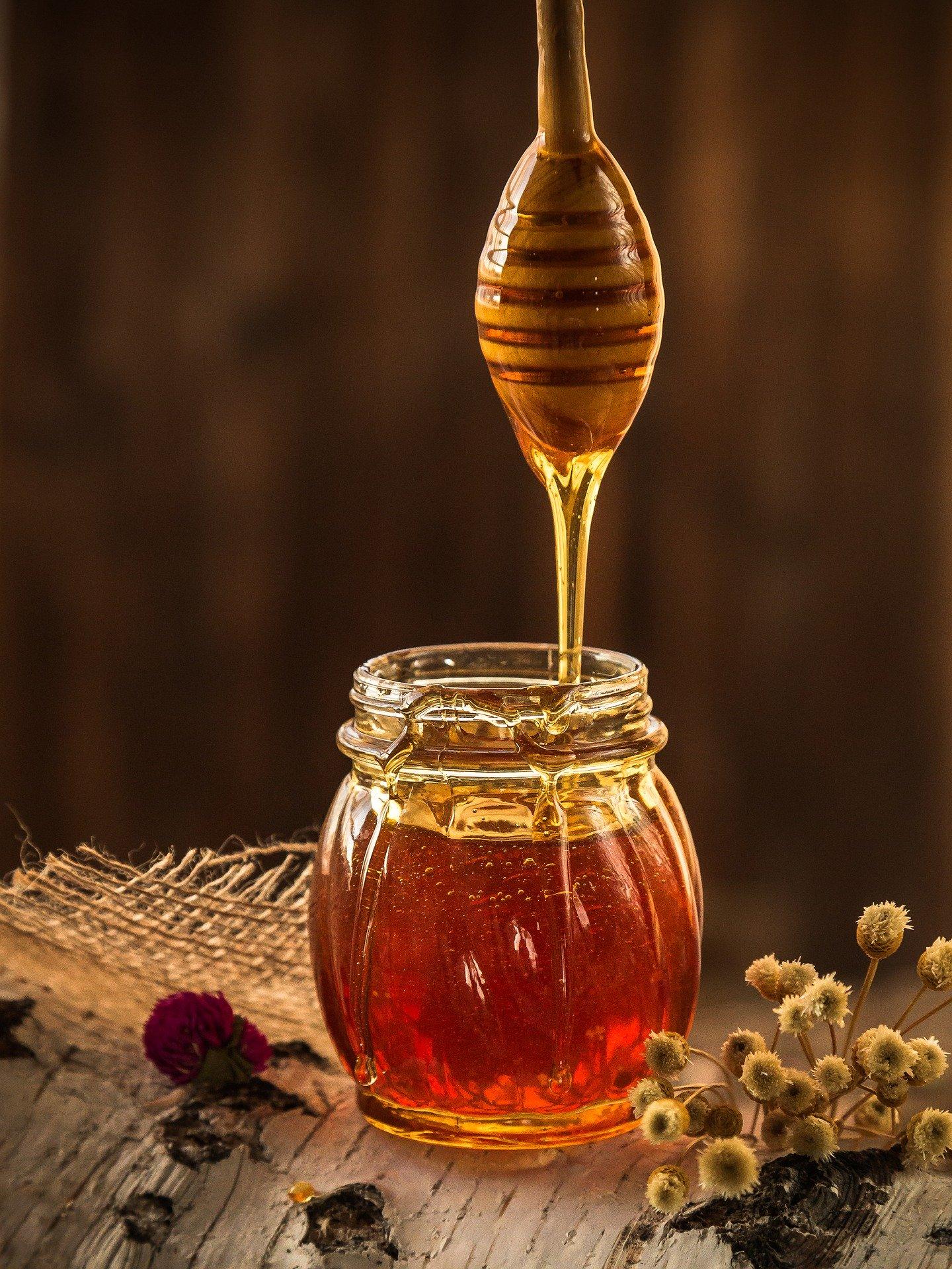 honey dripping into a jar